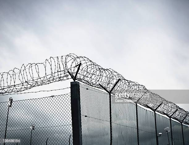 chain link fence with barbed wire and razor wire. - barbed wire stock pictures, royalty-free photos & images