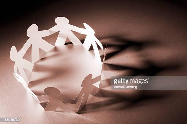 Kreis von Menschen Hände halten Papier-Kette im Scheinwerferlicht