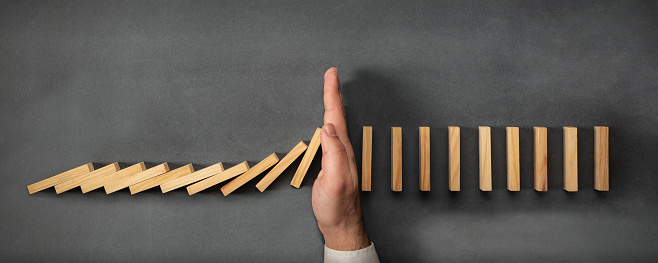 Chain Reaction In Business Concept, Businessman Intervening Dominoes Toppling 1126856471
