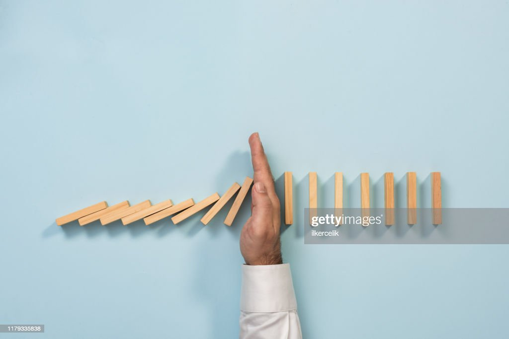 Chain Reaction In Business Concept, Businessman Preventing  Dominoes Continuous Toppling. : Stock Photo