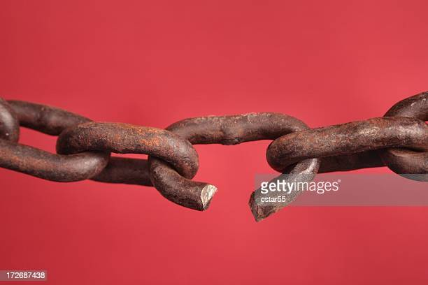 chain with broken link on red background - chain stock pictures, royalty-free photos & images