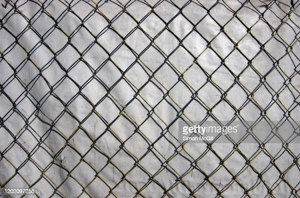 chainlink fence backed with white plastic hessian tarpaulin screen at a construction site - malla textil fotografías e imágenes de stock