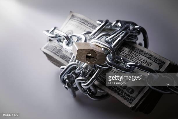 Chains and padlock around stack of dollar bills