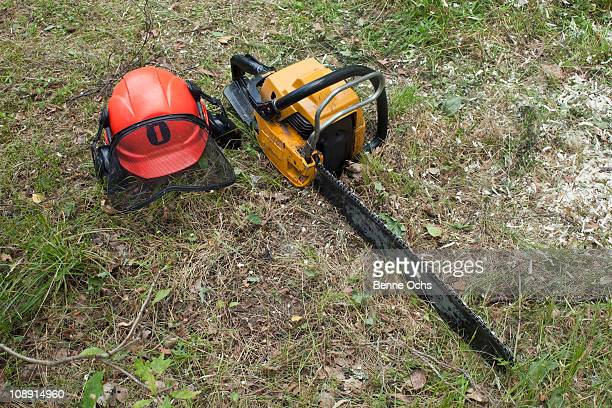 A chainsaw and safety helmet lying on the grass
