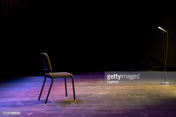 a chair and a microphone stand sitting on a stage with no people with dramatic lighting - stage performance space stockfoto's en -beelden