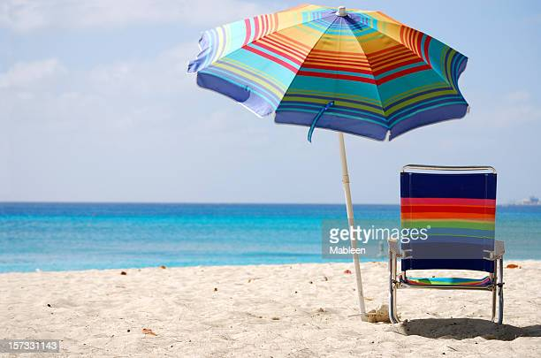 Chair and colorful umbrella on deserted beach