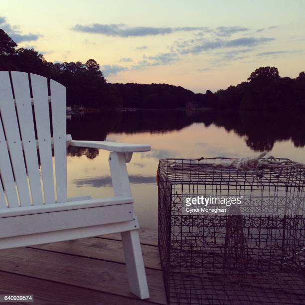 chair and crab trap at sunrise - crab pot stock photos and pictures