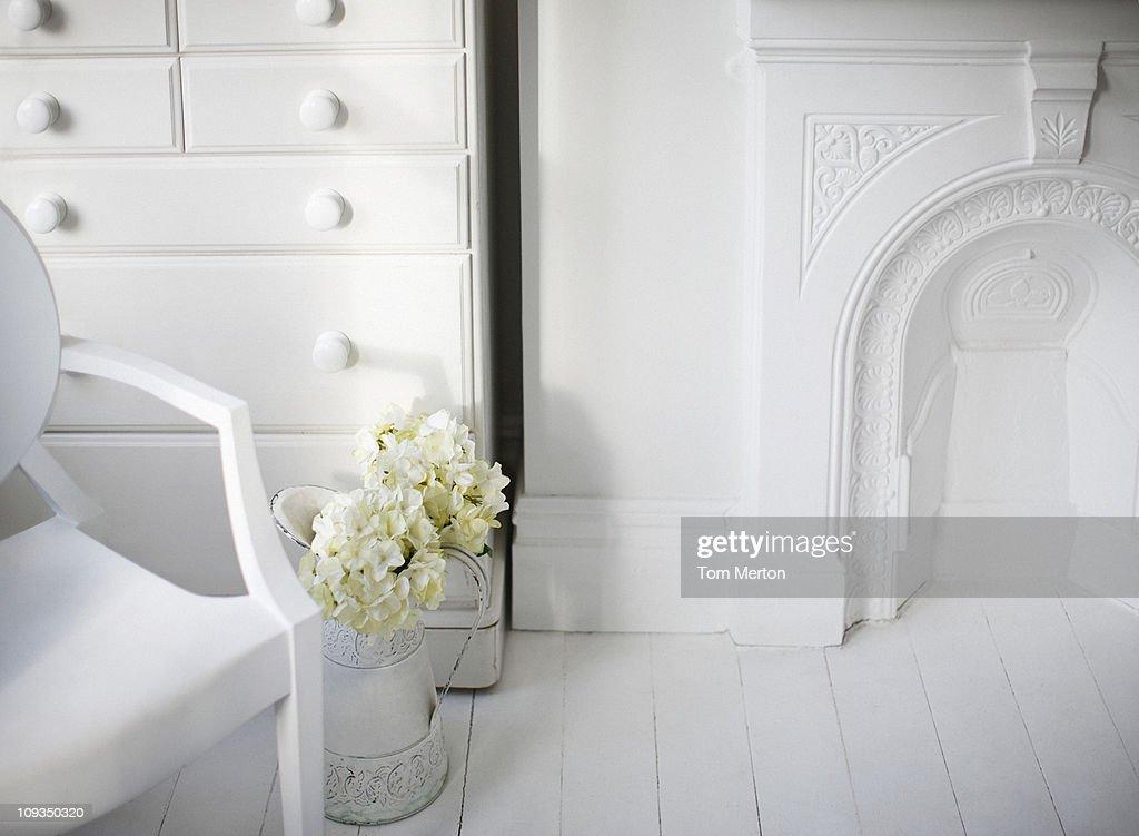 Stuhl und Kamin im eleganten weißen Wohnzimmer : Stock-Foto