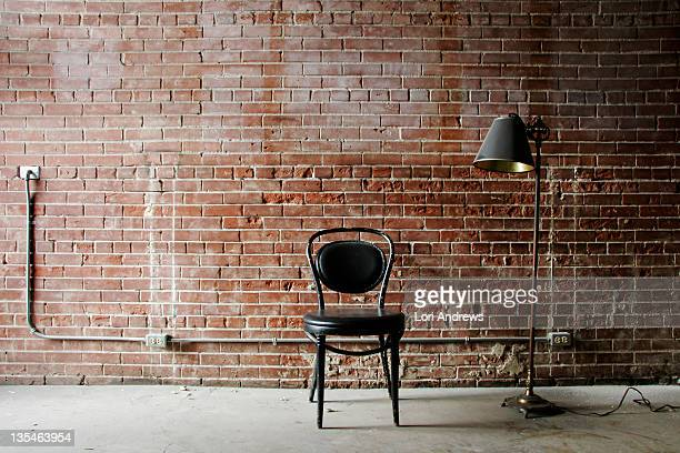 Chair and lamp against red brick wall