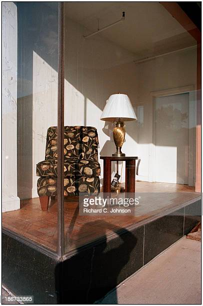 CONTENT] Chair and lamp table in discount furniture storefront window