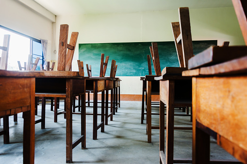 chair and table in class room with black board background, no student, school closed concept 1134900343