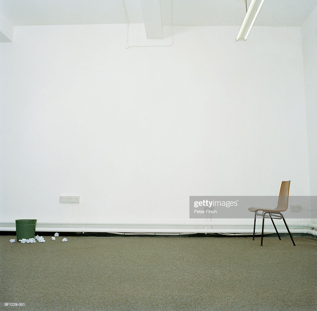 Chair and waste paper basket in office, bin surrounded by paper : Stock Photo