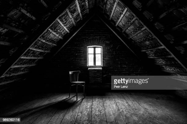 chair and window in empty attic in grayscale - 薄気味悪い ストックフォトと画像