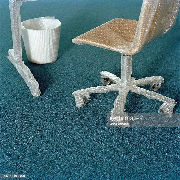 Chair, bin and desk wrapped in bubble wrap, close up