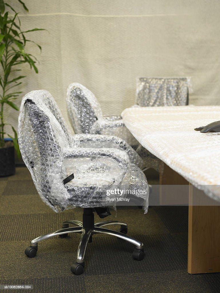 Chair Covered In Bubble Wrap By Conference Table : Stock Photo