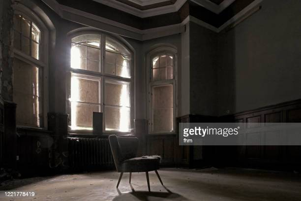 chair in an empty room in an abandoned building - banqueroute photos et images de collection