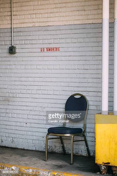 Chair in front of a painted stone wall below a non smoking sign
