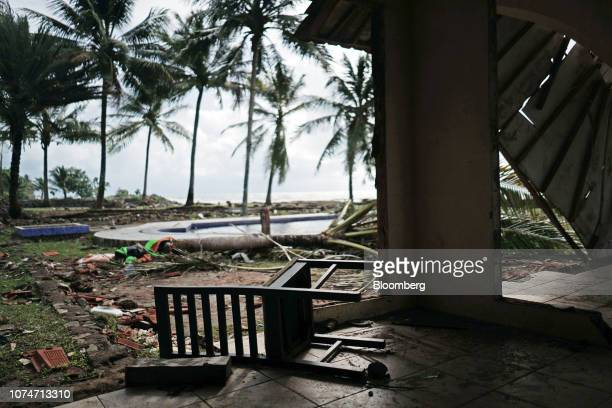 A chair lies on a ground among other debris next to a swimming pool at the Milla House Anyer hotel in Carita Banten province Indonesia on Monday Dec...