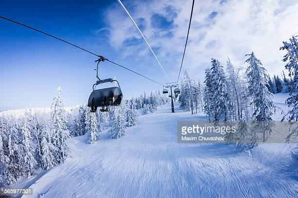 Chair lift gondolas over snowy slopes