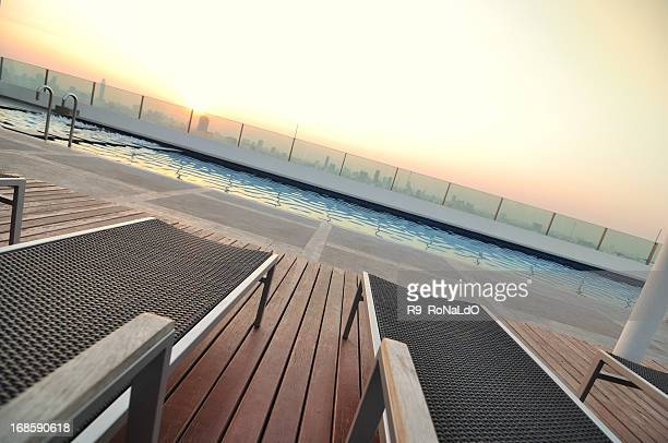 Chair near roof top swimming pool at sunset