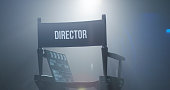Chair of director with clapboard in spotlight