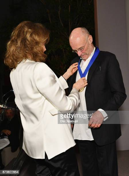 Chair of the Board of Trustees of the J Paul Getty Trust Maria HummerTuttle places the Getty Medal Award on Anselm Kiefer onstage during the Getty...