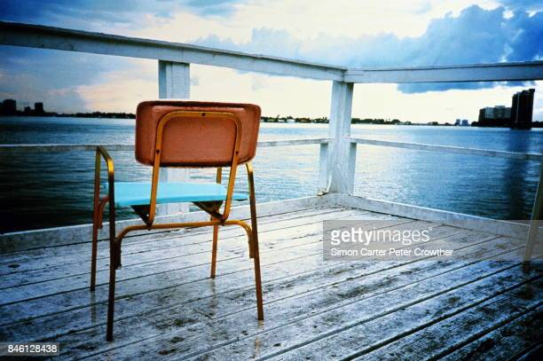 Chair on wooden jetty, city in background.