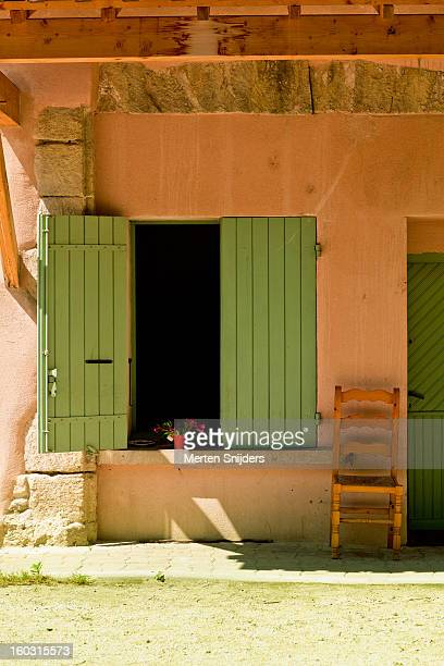 Chair outside home with green shutters
