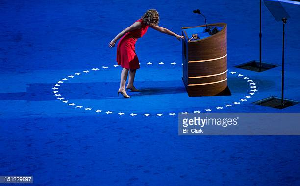 DNC chair Rep Debbie Wasserman Schultz DFla appears to get her heel caught in the carpet on stage during her podium walk through at Time Warner Cable...