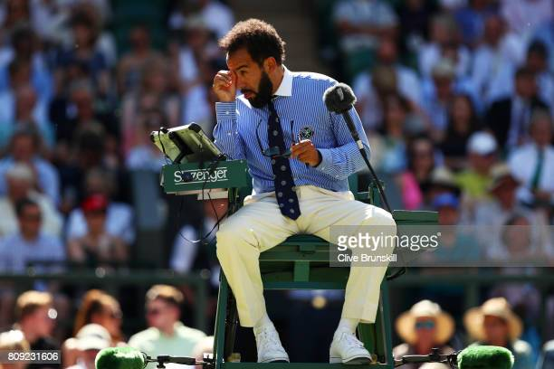 Chair umpire Kader Nouni is pestered by flying ants during the Ladies Singles second round match between Johanna Konta of Great Britain and Donna...