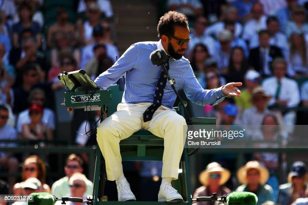Chair umpire Kader Nouni swats flying ants during the Ladies Singles second round match between Johanna Konta of Great Britain and Donna Vekic of...