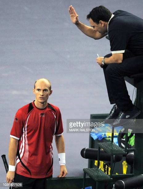 Chair umpire Mohamed Lahyani gestures while discussing a line call with Nikolay Davydenko of Russia during the men's singles final against Novak...