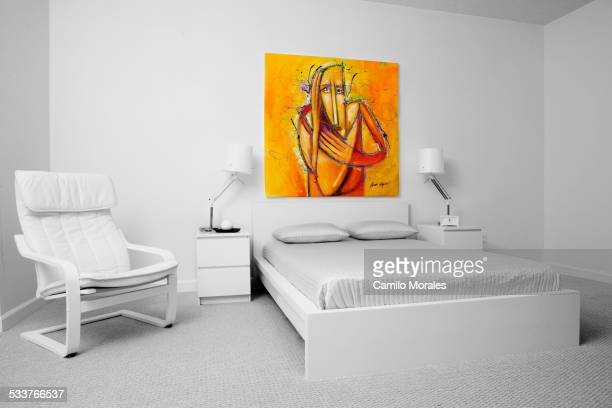 Chair, wall art and bed in modern bedroom