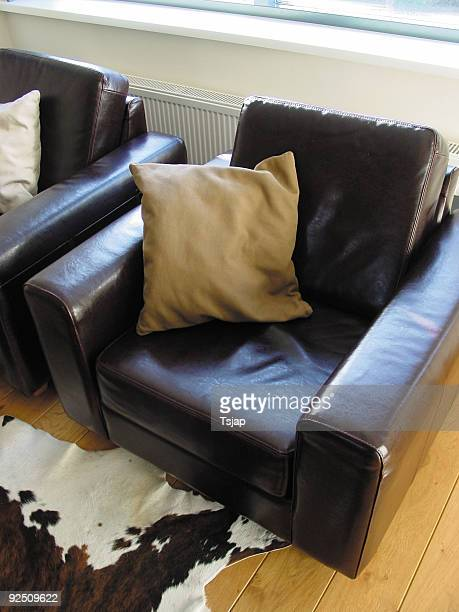 chair with pillow - cowhide stock photos and pictures