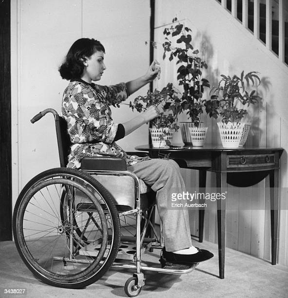 Chairbound actress Pamela Russell attending to indoor plants in her home.