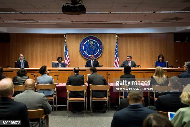 FCC Chairman Ajit Pai and commission members take their seats for a hearing at the Federal Communications Commission on December 14 2017 in...