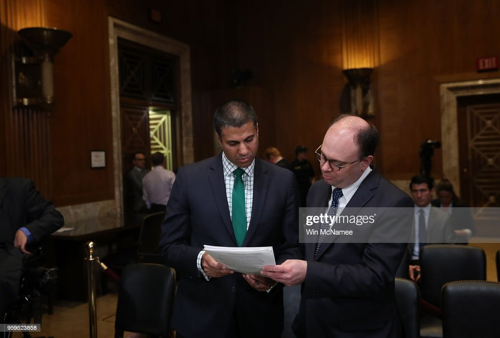 Chairman Ajit Pai (L) confers with an aide prior to testimony before the Senate Appropriations Committee May 17, 2018 in Washington, DC. The committee heard testimony on the proposed budget estimates and justification for fiscal year 2019 for the Federal Communications Commission and the Federal Trade Commission.
