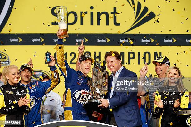 NASCAR chairman and CEO Brian France presents Brad Keselowski driver of the Miller Lite Dodge with the series trophy in Champions Victory Lane after...