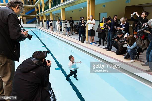Chairman and CEO of Accor Sebastien Bazin is surrounded by the medias after a swim in the winter pool at the Piscine Molitor during its inauguration...