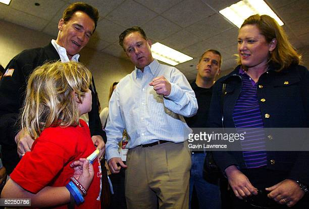 Chairman and CEO of NASCAR Brian France talks with California governor Arnold Schwarzenegger and his son Christopher during the NASCAR Nextel Cup...