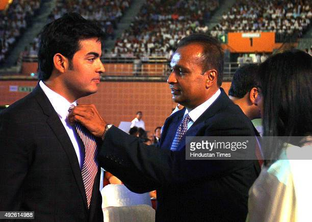 ADAG chairman Anil Ambani adjusts the tie of his nephew and Mukesh Ambanis son Anant Ambani before the launch of Digital India Week by Prime Minister...