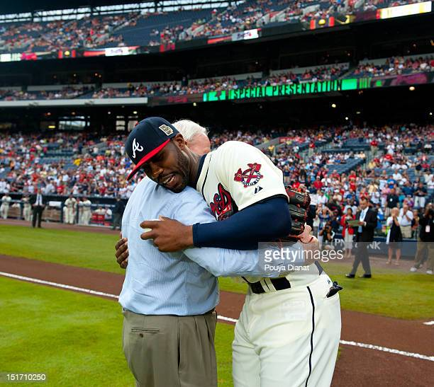 Chairman Emeritus of the Atlanta Braves Bill Bartholomay hugs Jason Heyward of the Atlanta Braves after throwing out the ceremonial first pitch...