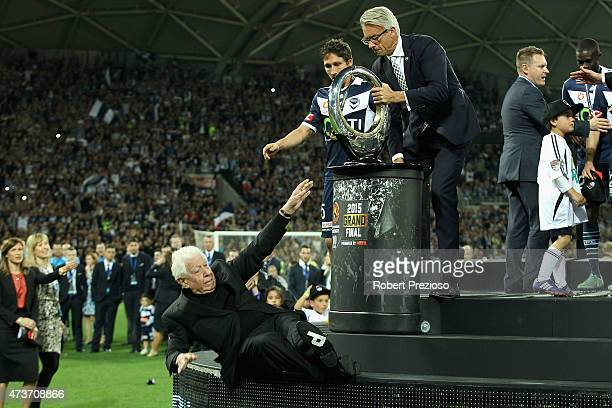 FFA chairman Frank Lowy falls off the stage as he presents Victory with the winners trophy during the 2015 ALeague Grand Final match between the...