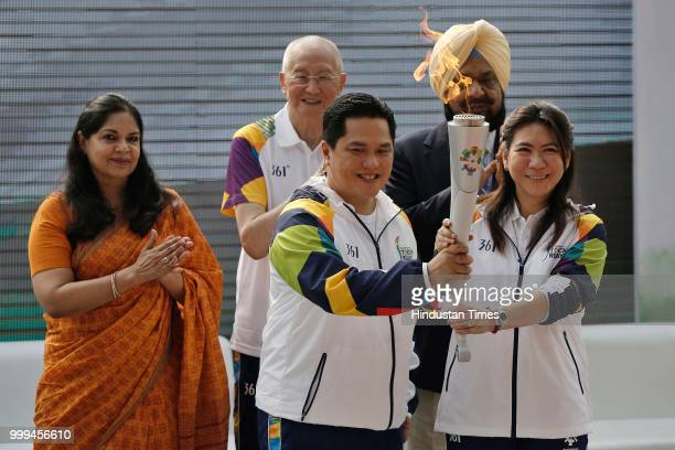 Chairman Indonesia Asian Games Organizing Committee Erick Thohir Badminton legend Susi Susanti hold the torch during the 'Torch Relay' begins for the...