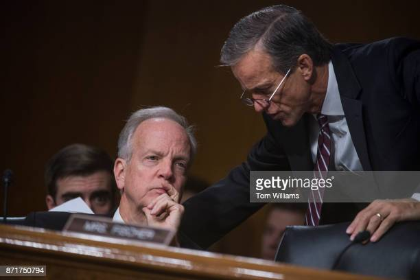 Chairman John Thune RSD right talks with Sen Jerry Moran RKan during a Senate Commerce Science and Transportation Committee hearing titled...