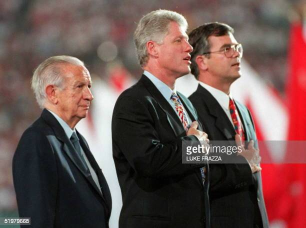 Chairman Juan Antonio Samaranch flanks US President Bill Clinton and ACOG President and CEO Billy Payne while they sing the US national anthem during...