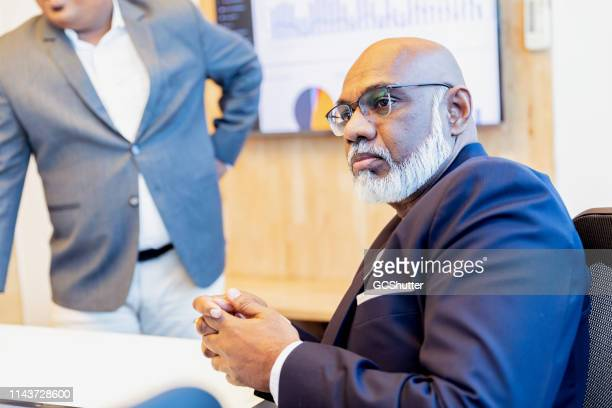 chairman listening to his board of advisors in a group meeting - chairperson stock pictures, royalty-free photos & images
