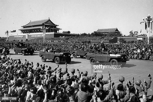 Chairman Mao Zedong driving past a meeting of Red Guards and the revolutionary teachers and students who are holding up copies of his Little Red Book...