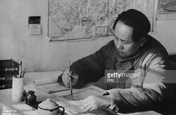 Chairman Mao Zedong of the Communist Party of China writing with a brush at his desk in a cave headquarters in north-west China during the Chinese...