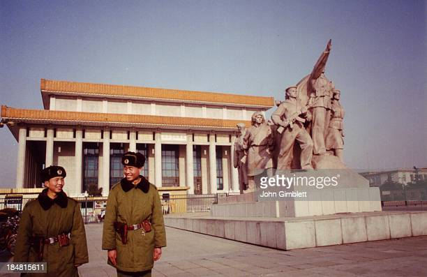 Chairman Mao's mausoleum in his centenary year, 1992. Two soldiers, one male one female, share a laugh near a sculpture.